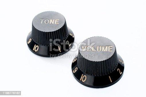 Vintage black guitar volume and tone knobs on white background