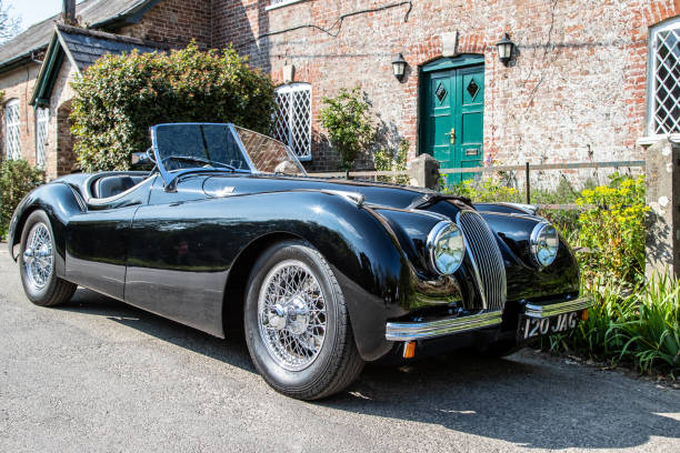 Vintage black Jaguar sports car Moreton, UK - 20 April 2019: Pristine vintage black Jaguar sports car parked in the village of Moreton, Dorset, UK jaguar car stock pictures, royalty-free photos & images
