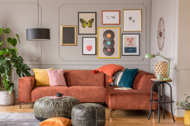 Vintage black poufs in trendy eclectic living room interior with brown couch stock photo