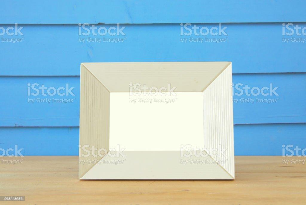 Vintage blank white photo frame over wooden table. Ready for photography montage. - Zbiór zdjęć royalty-free (Antyczny)