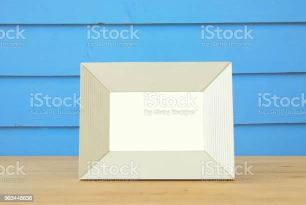 Vintage Puste Białe Ramki Na Drewniany Stół Gotowy Do Montażu Fotografii - zdjęcia stockowe i więcej obrazów Antyczny