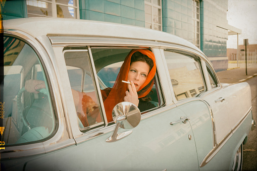 Woman in a red head scarf in her 20s smokes a cigarette and looks out an open car window while driving a vintage pale blue and white car stopped at an intersection, Evansville, IN, USA