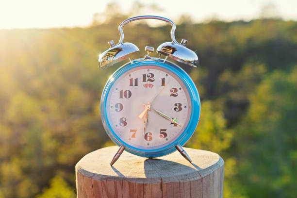 Vintage blue alarm clock on summer forest background Vintage blue alarm clock on summer forest background. Daylight saving time concept winter time fresh start morning stock pictures, royalty-free photos & images