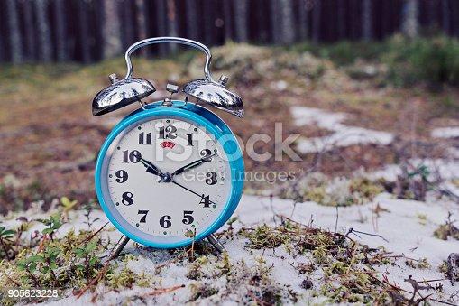 905623256 istock photo Vintage blue alarm clock on winter forest background 905623228