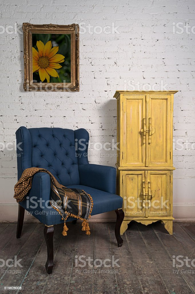 Vintage blue armchair, yellow cupboard and framed painting stock photo