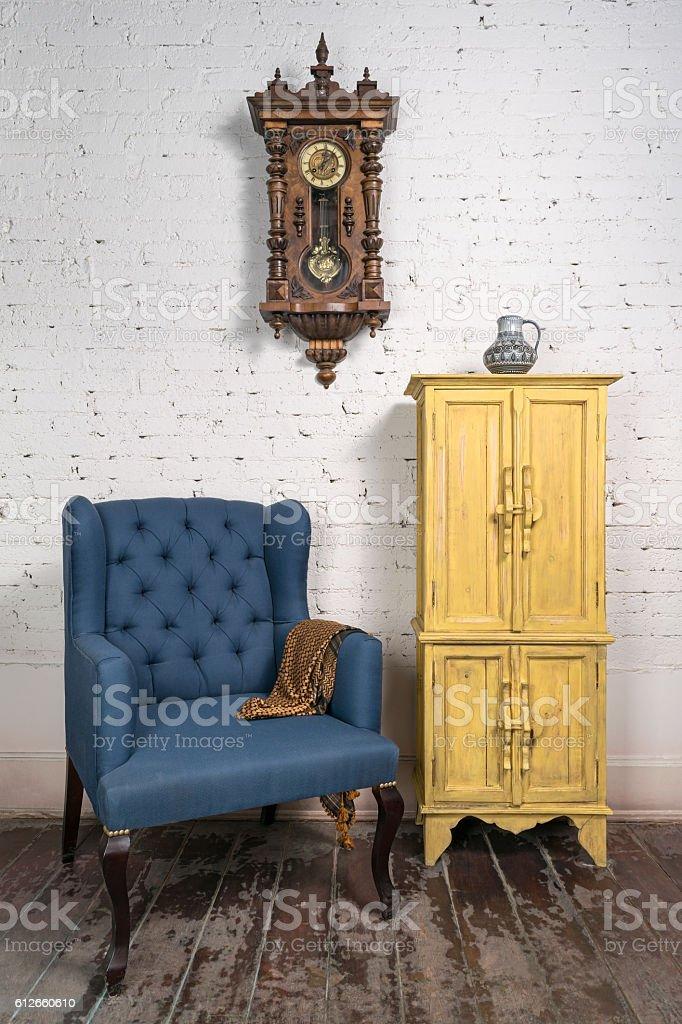 Vintage blue armchair, yellow cupboard, pendulum clock and orange scarf stock photo