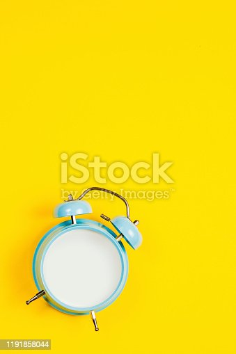 816405814 istock photo Vintage blue blank alarm clock on a yellow background with marskmallows as a decoration 1191858044