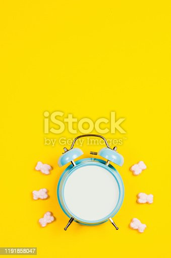 816405814 istock photo Vintage blue blank alarm clock on a yellow background with marskmallows as a decoration 1191858047