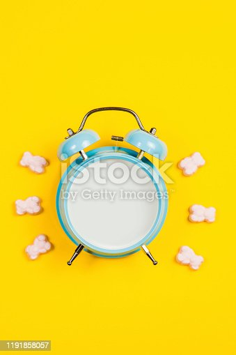 816405814 istock photo Vintage blue blank alarm clock on a yellow background with marskmallows as a decoration 1191858057