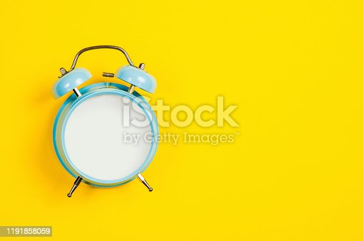 816405814 istock photo Vintage blue blank alarm clock on a yellow background with marskmallows as a decoration 1191858059