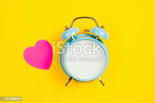 816405814 istock photo Vintage blue blank alarm clock on a yellow background with pink sticker 1191858043