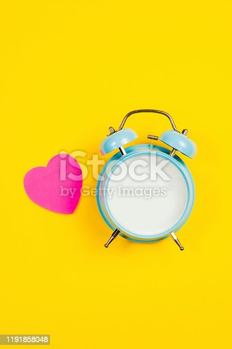 816405814 istock photo Vintage blue blank alarm clock on a yellow background with pink sticker 1191858048
