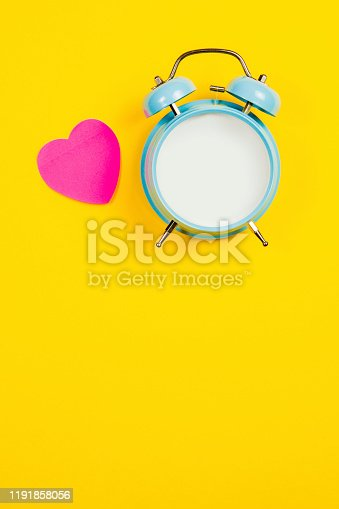 816405814 istock photo Vintage blue blank alarm clock on a yellow background with pink sticker 1191858056