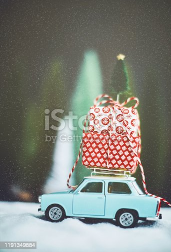 Vintage blue car transporting Christmas gifts in snowy scene. Christmas holiday background.