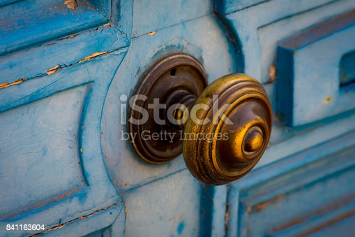 Vintage blue door with patina and brass knob