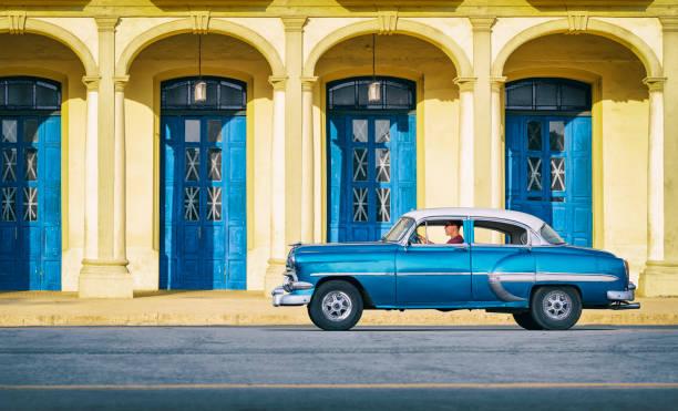 Vintage blue oldtimer car driving through Old Havana Cuba stock photo