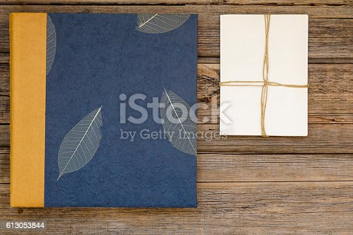 Vintage blue photo album or photo book with vintage style stack of blank photos on a rustic wood background