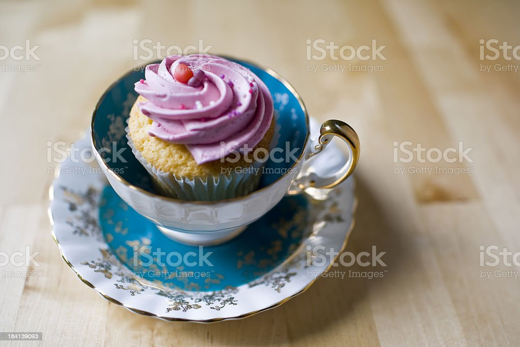 A vintage blue teacup holding a pink frosted cupcake. stock photo