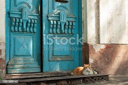 Vintage blue wooden door in yellow stone wall. Blue double door. Aged wooden door with blue paint and door handles.