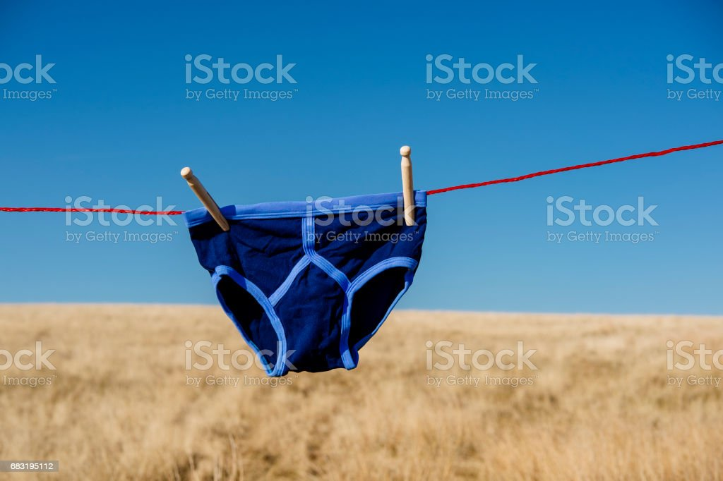 Vintage blue Y-front underwear on a washing line. stock photo