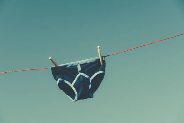 vintage blue y-front underwear on a washing line. - washing line stock photos and pictures