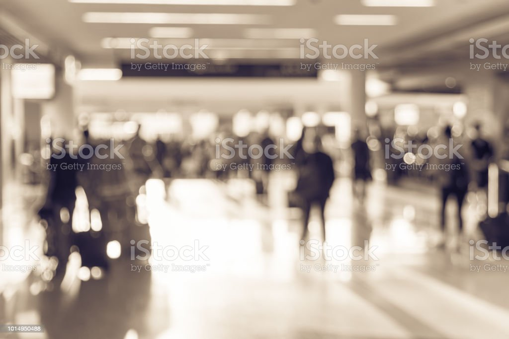 Vintage tone blurred busy group of people walking at airport with...