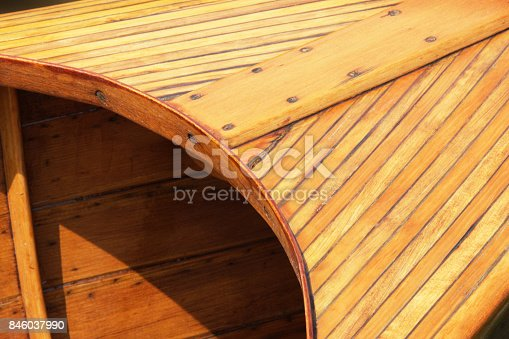 Antique boat hull detail, varnished wood and brass screws, severely weathered,  tightly cropped with angles and curves.