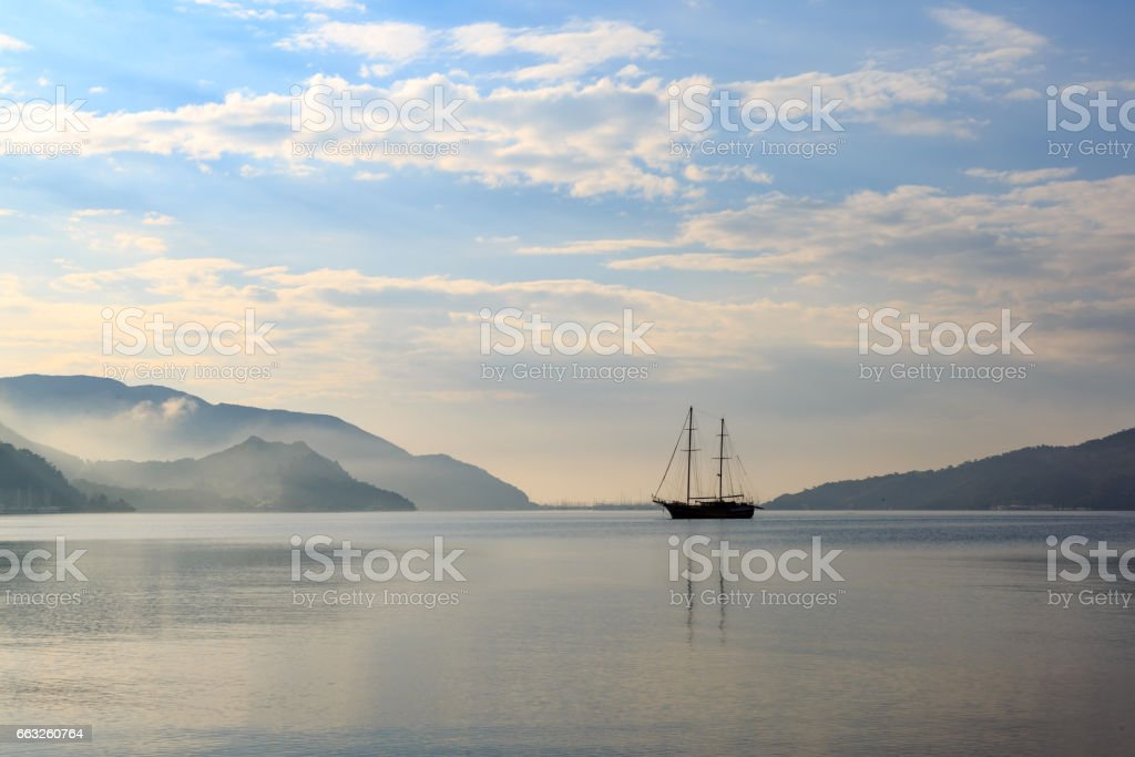 Vintage boat in misty weather with reflection stock photo