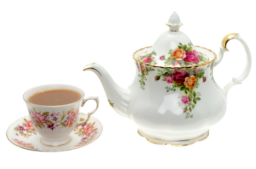 Vintage bone China teapot with a cup of tea - studio shot with a white background