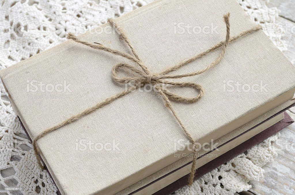Vintage book bundle tied up with twine on lace doily royalty-free stock photo