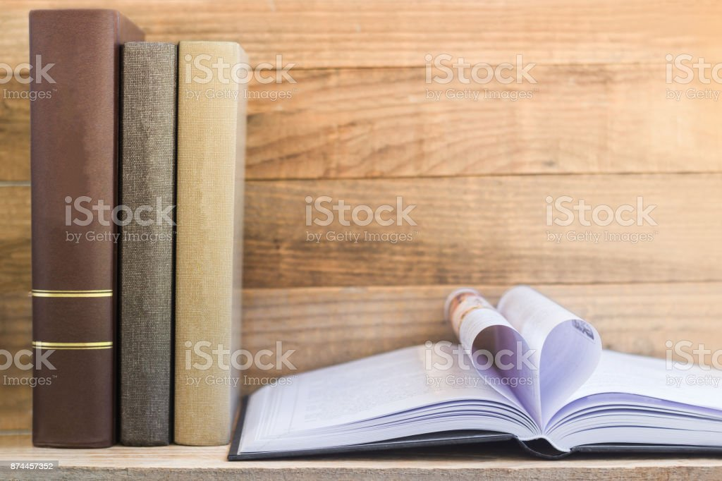 Vintage Books And Open Book On Wooden Shelf. stock photo