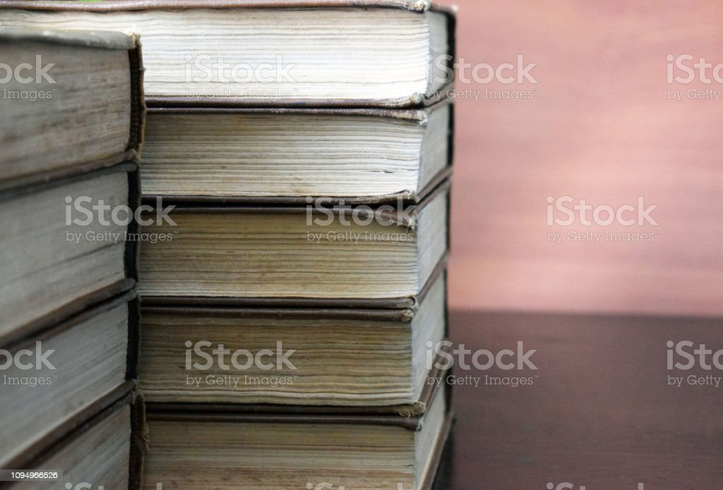 Vintage books lie on a wooden table. Classical literature. Old faded...