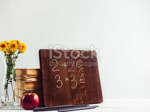 istock Vintage books, old clock, pencils, red apple and blackboard 1018374594