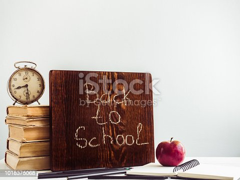 istock Vintage books, old clock, pencils, red apple and blackboard 1018375068