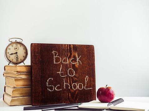 1045293630 istock photo Vintage books, old clock, pencils, red apple and blackboard 1018375068