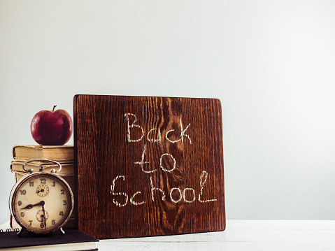 1045293630 istock photo Vintage books, old clock, pencils, red apple and blackboard 1018375178