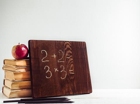 1045293630 istock photo Vintage books, old clock, pencils, red apple and blackboard 1018375230