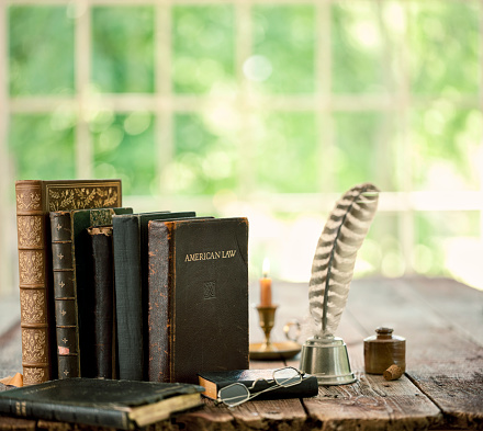Vintage study area with books, quill pen and candle on an old wood desk in front of a window