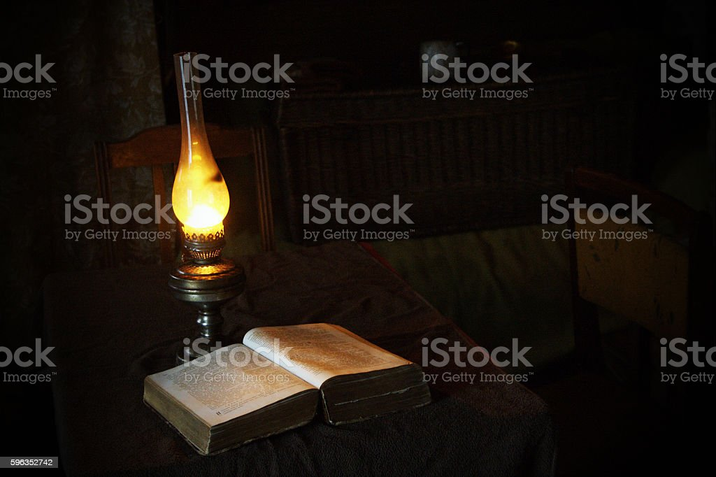 Vintage books opened for reading with ancient lamp stock photo