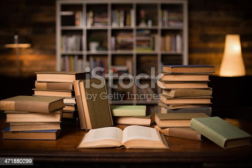 istock Vintage Books Sitting on Old Desk, With Shelved Wall Background 471880299