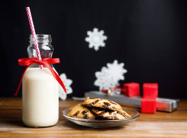 vintage milchflasche mit rotem band und weihnachtsmänner cookies auf holztisch über schwarz - rustikale einweckgläser stock-fotos und bilder