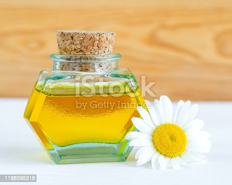 istock Vintage bottle with roman chamomile essential oil (extract, tincture, infusion). Aromatherapy, spa and herbal medicine concept. Copy space. 1198595318