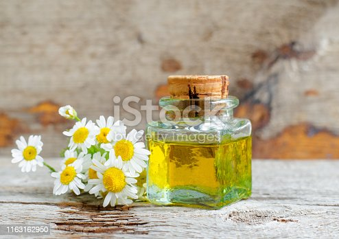 istock Vintage bottle with roman chamomile essential oil (extract, tincture, infusion). Old wooden background. Aromatherapy, spa and herbal medicine concept. Copy space. 1163162950