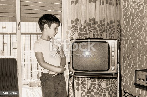 Vintage  black and white photo boy looking at an old tv