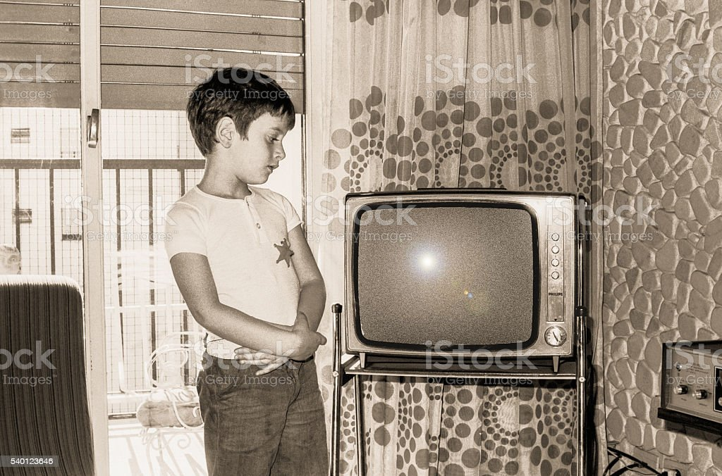 Vintage boy looking at an old tv stock photo