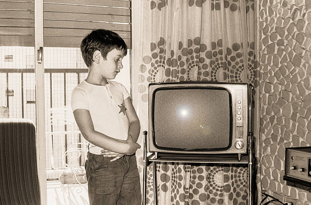vintage boy looking at an old tv - 1970s style stock photos and pictures