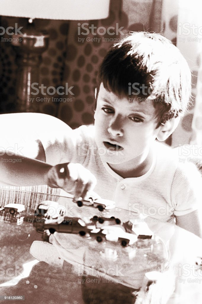 Vintage boy playing with toy cars stock photo