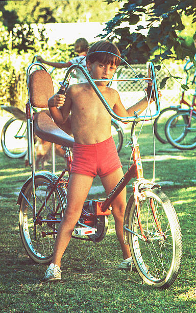 vintage boy with his bicycle - 1970s style stock photos and pictures
