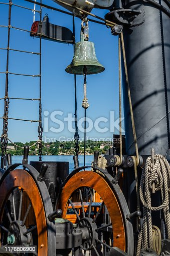Vintage brass ship's bell above ship's wheel and next to main mast with the St. Lawrence River coastline in the distance.