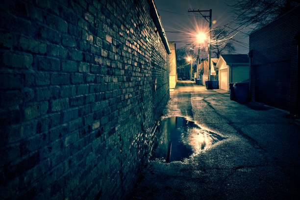 Vintage brick wall in a dark, gritty and wet Chicago alley at night after rain. stock photo